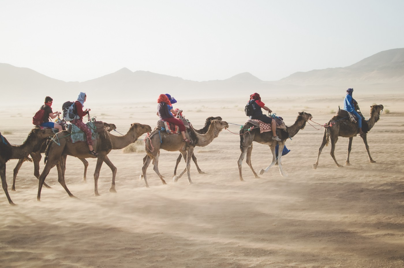 A family riding through the desert on camels